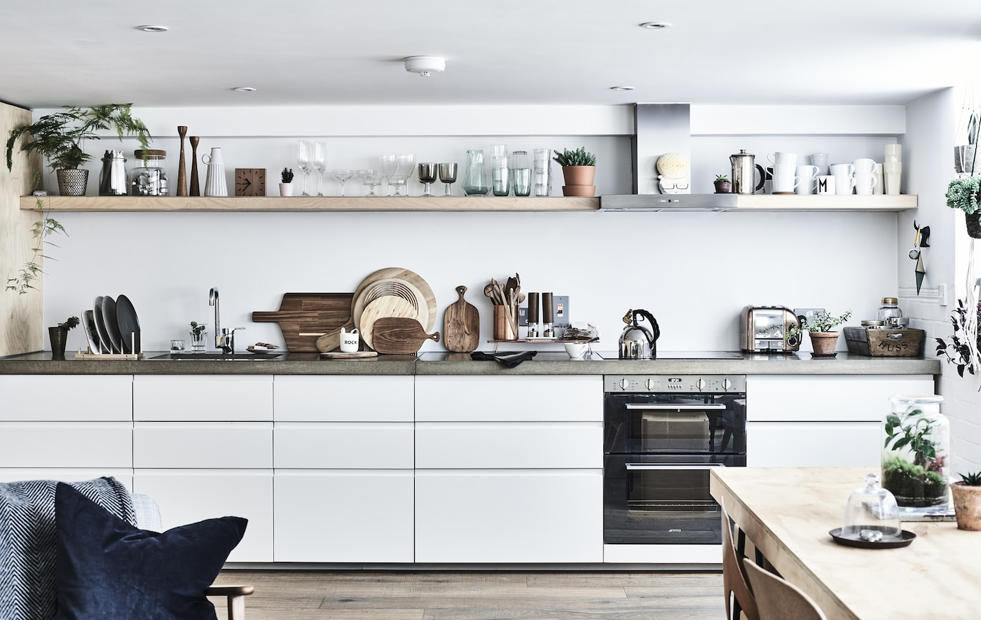 Bela kuhinja s betonskom radnom pločom i policama.