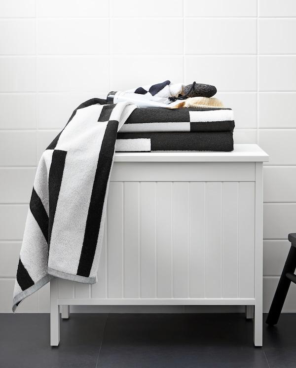 Bela SILVERÅN klupa za odlaganje s peškirima i crno-belom grafičkom šarom na vrhu, u kupatilu.