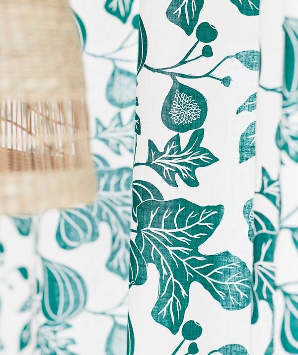 Bela zavesa sa zelenom šarom u obliku grane masline, pored plafonske lampe od prirodnih vlakana banane.