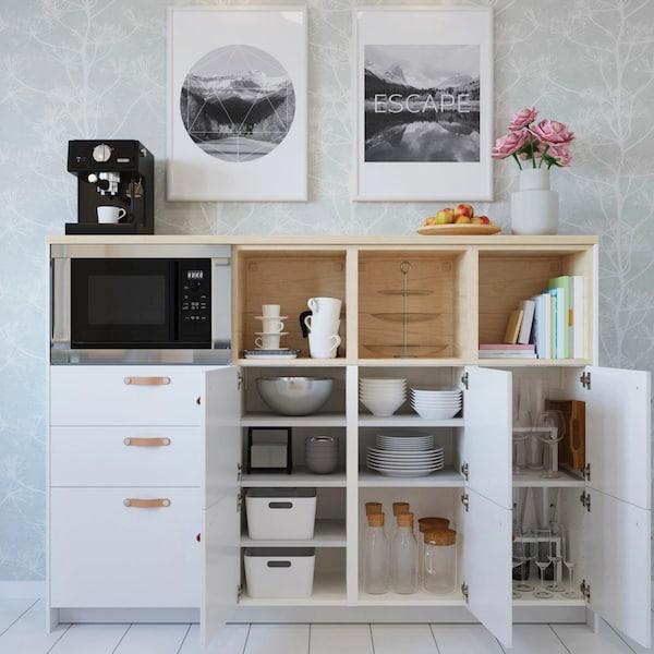 Белая кухня КНОКСХУЛЬТ с деревянной столешницей, на полу лежит ковер, рядом белая духовка, над ней стальная вытяжка.