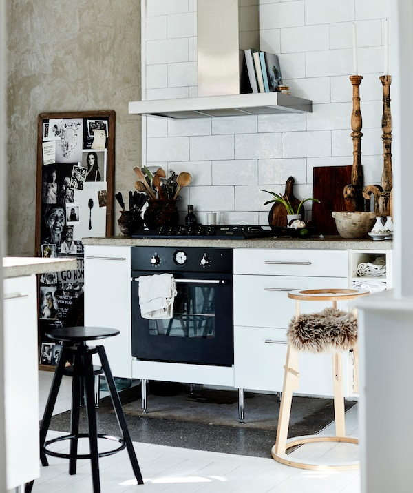Белая кухня с вытяжкой, белой плиткой на стенах и деревянными аксессуарами.