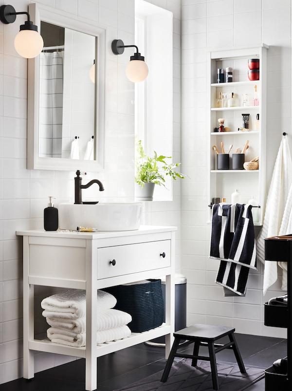 Beli HEMNES kupatilski nameštaj s jednom fiokom, jednom policom s peškirima i HAMNSKÄR kombinovanom slavinom, ogledalom, i dve lampe.
