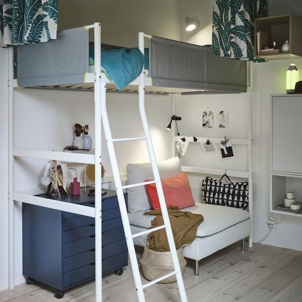 Beli izdignuti krevet sa sivim šinama, a ispod je beli jednosed, plavi fiokar i oslonac za laptop.