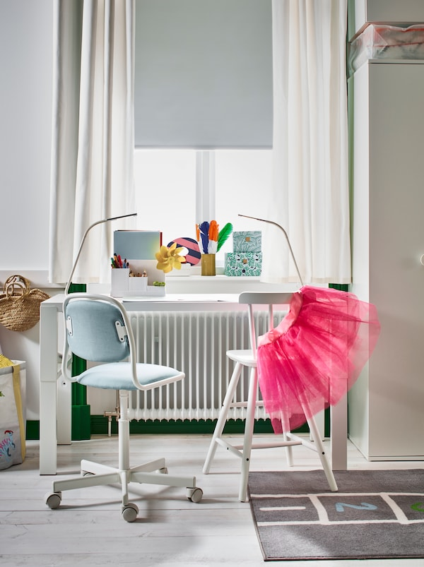 Beli PÅHL pisaći sto i AGAM dečja stolica pored osunčanog prozora u svetloj dečjoj sobi s drvenim podom.