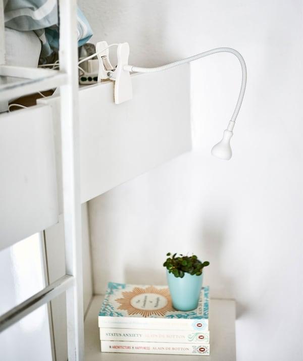Beli podesivi reflektor sa štipaljkom, usmeren ka gomili knjiga na polici.