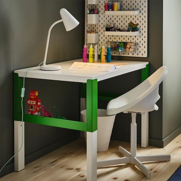 Beli/zeleni pisaći sto, bela radna lampa, bela perforirana ploča s dodacima, farba u bocama i bela dečja radna stolica.