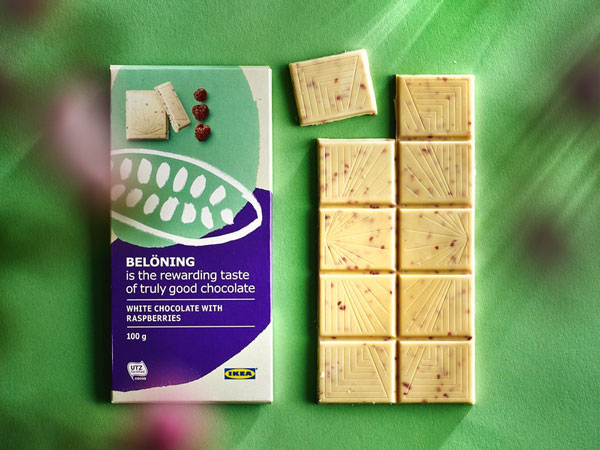 BELÖNING white chocolate with rasperries on a green background.