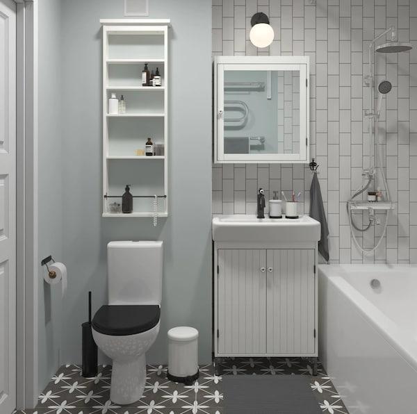 Белый зеркальный шкаф ХЕМНЭС над белым шкафом для раковины с двумя выдвижными ящиками, рядом высокий шкаф со стеклянной дверцей.