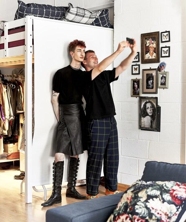 Ben e Donald facéndose un selfie xunto á cama alta, xunto a unha parede chea de cadros.