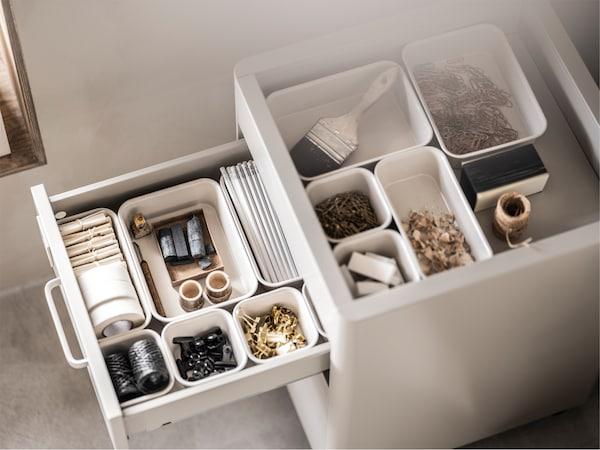 Beo element za odlaganje s otvorenom fiokom i otvorenim vrhom, s bež NOJIG kutijama u različitim veličinama, za sitne predmete.