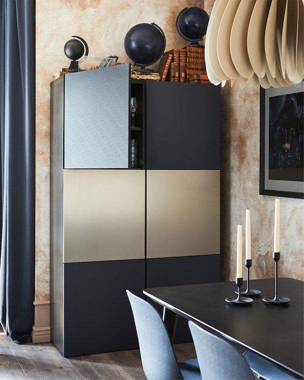 BESTÅ kombinacija za odlaganje u crnobraon boji s plavim vratima, iza trpezarijskog stola sa svećama i nekoliko stolica.