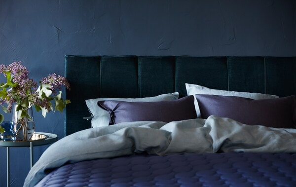 Bett mit einem mit dunkelgrünem Samt überzogenen Kopfteil und ein Beistelltisch mit frischen Blumen daneben.