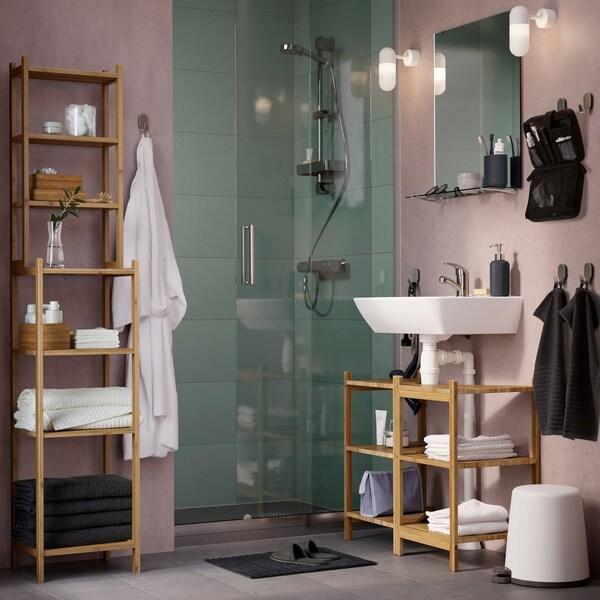Bež i sivo kupatilo s RÅGRUND umivaonikom/ugaonom policom i spojenim policama od bambusa.