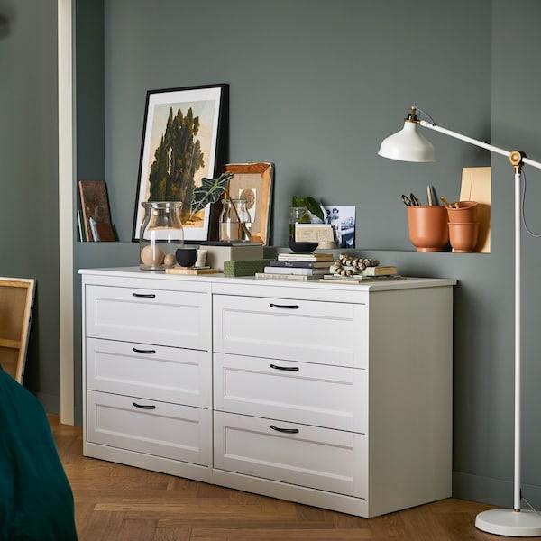 Biała komoda BRUSALI z sześcioma szufladami w szarej sypialni.
