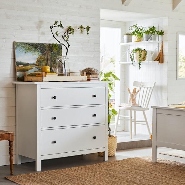 Biała komoda HEMNES w jasnej, białej sypialni.