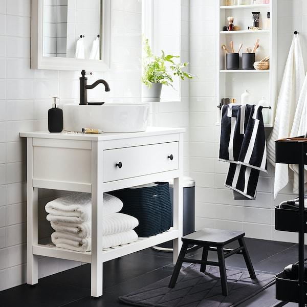 Biała łazienka z oknem i szafką z umywaką z serii HEMNES.