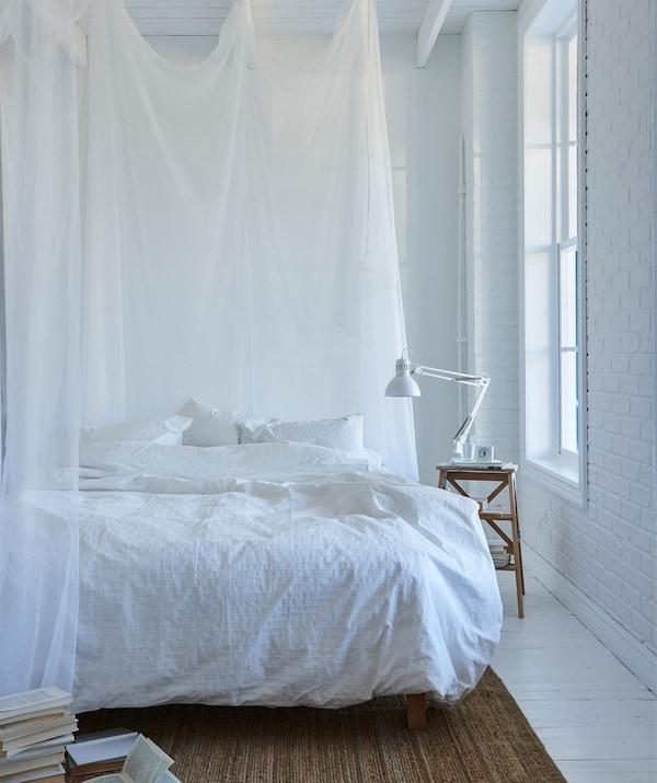 Biała sypialnia z białą pościelą i przezroczystymi białymi zasłonami wokół łóżka.