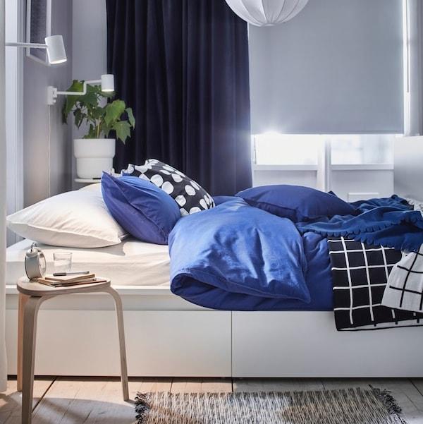 Biała sypialnia z białym łożkiem MALM i niebieskimi dodatkami.