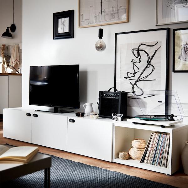 Biała szafka pod telewizor z czarnymi uchwytami, czarny telewizor, czarny głośnik, szary dywan i oprawione plakaty różnej wielkości.