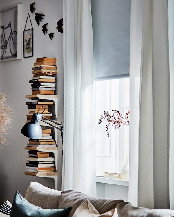 Białe drewniane półeczki na książki, białe zasłony i biała roleta zaciemniająca zakrywająca okno do połowy.