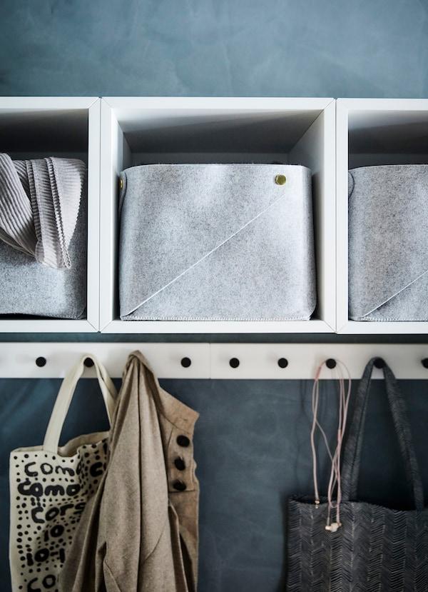 Białe otwarte szafki IKEA EKET z filcowymi pojemnikami w środku oraz torby na zakupy zawieszone na haczykach poniżej.