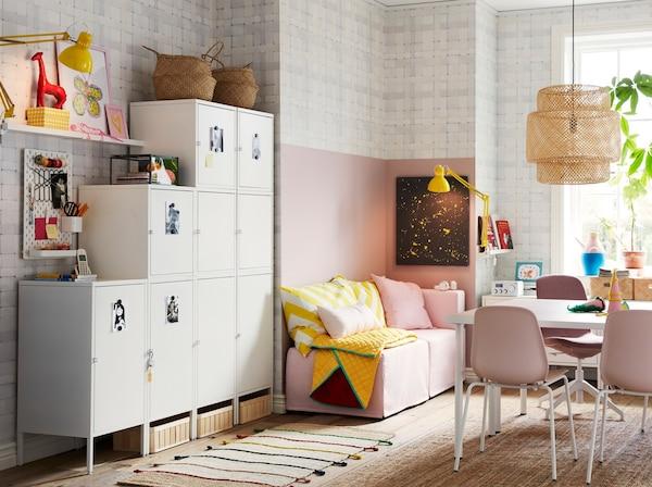 Białe szafki HÄLLAN umieszczone przy ścianie, używane do przechowywania w kompaktowej, rodzinnej przestrzeni dziennej w kolorach różowym, białym i żółtym.
