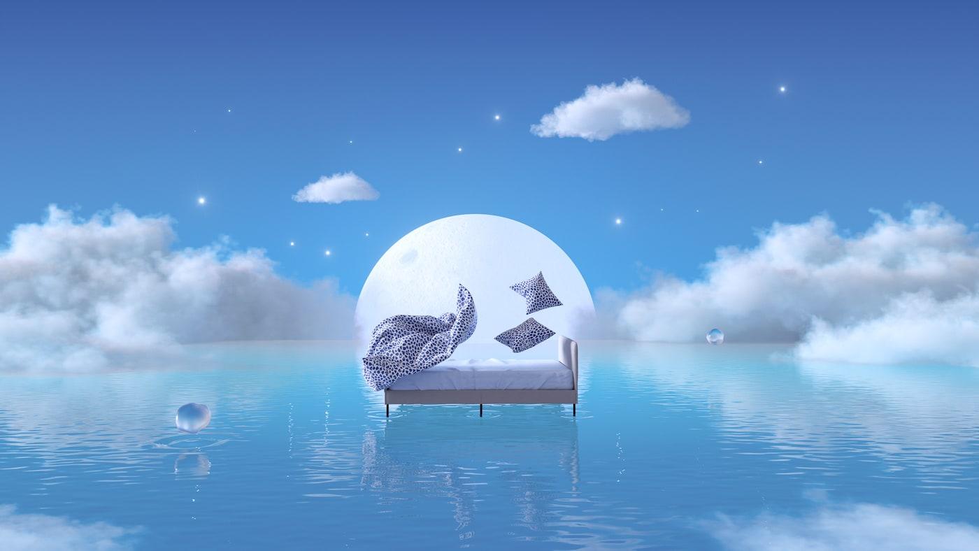 Biało-granatowa, cętkowana pościel KVASTFIBBLA opadająca na łóżko SLATTUM, które unosi się nad niebieską wodą na tle wschodzącego księżyca.