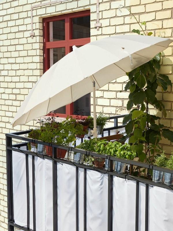 Biały parasol SAMSÖ/GRYTÖ odchylony tak, by chronił przed słońcem i zapewniał cień.