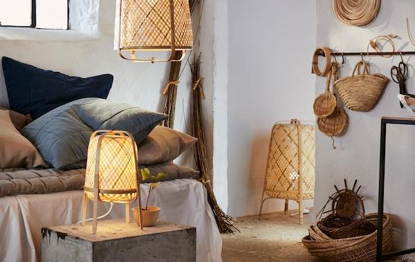 Biały pokój z neutralnymi tekstyliami, rattanowymi koszami oraz lampą podłogową, lampą stołową i lampą wiszącą z bambusa.