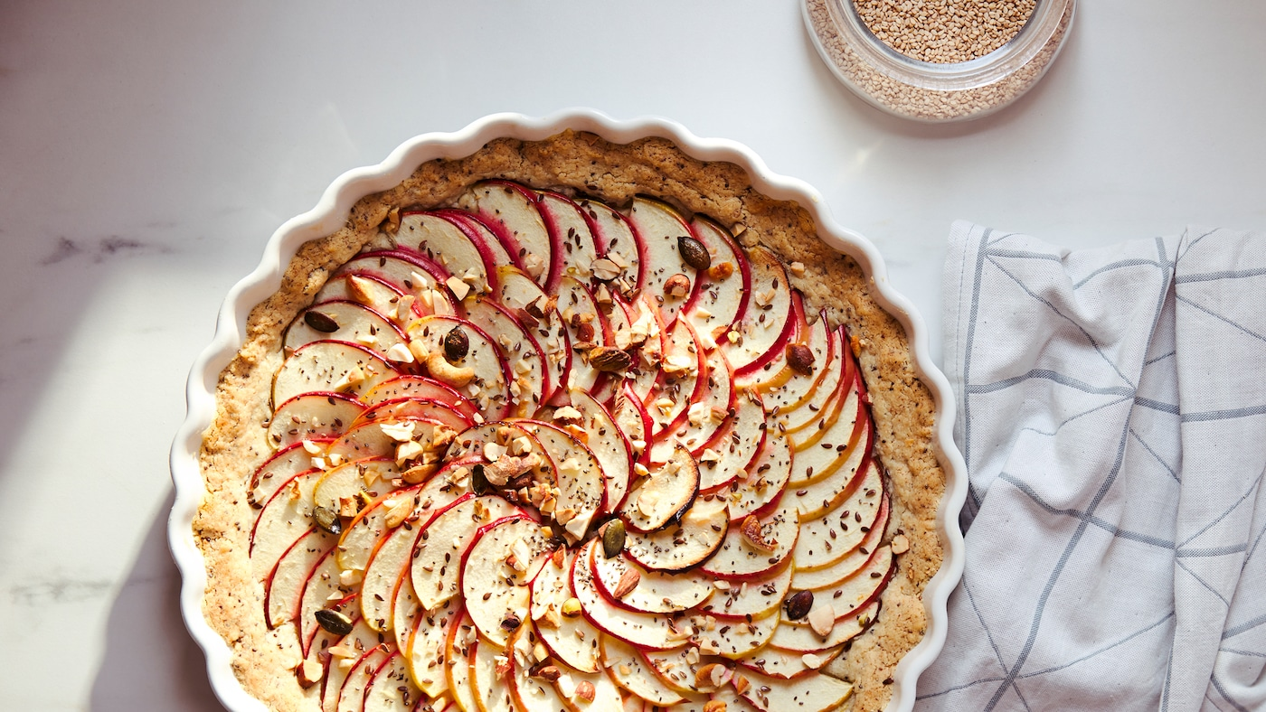 Biały ręcznik kuchenny z szarym wzorem i upieczone w białej formie do pieczenia VARDAGEN ciasto z ułożonymi na wierzchu plastrami jabłek.