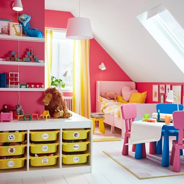 Biały regał TROFAST z dziewięcioma żółtymi, plastikowymi półkami na pojemniki w jaskrawo różowym pokoju dziecięcym.