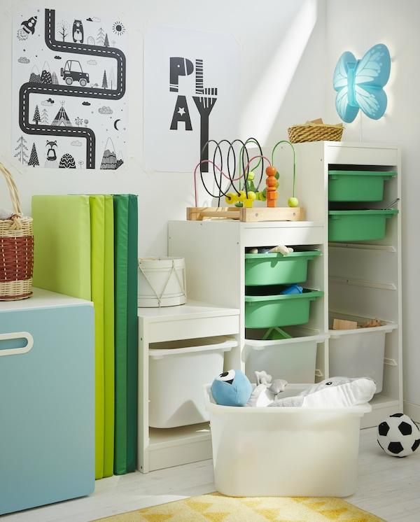 Biały regał TROFAST z zielonymi i białymi pojemnikami różnej wielkości, złożona zielona mata gimnastyczna, dwa plakaty na ścianie i żółty dywan.