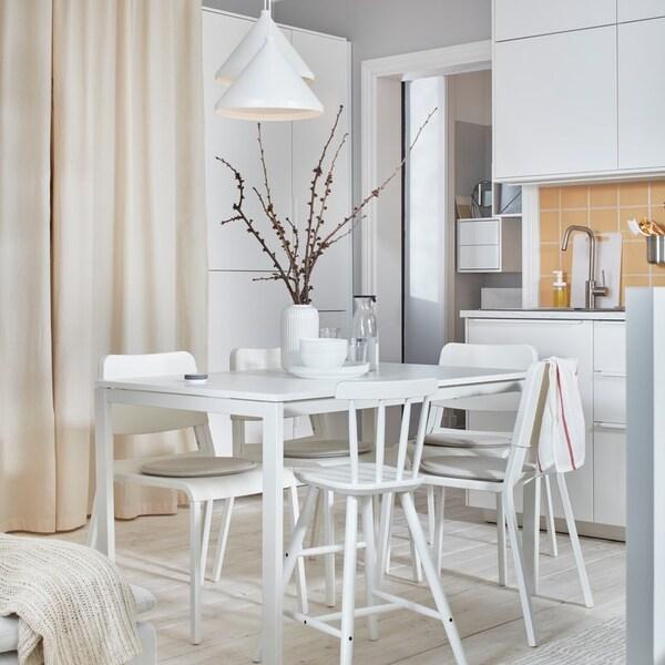 Biały stół jadalniany z białymi krzesłami przy kuchni z białymi frontami.