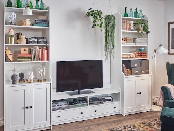 Biały zestawy mebli do przechowywania HAUGA złożony z dwóch wysokich szafek i szafki pod telewizor. Ustawiono na nich telewizor, konsolę do gier i książki.