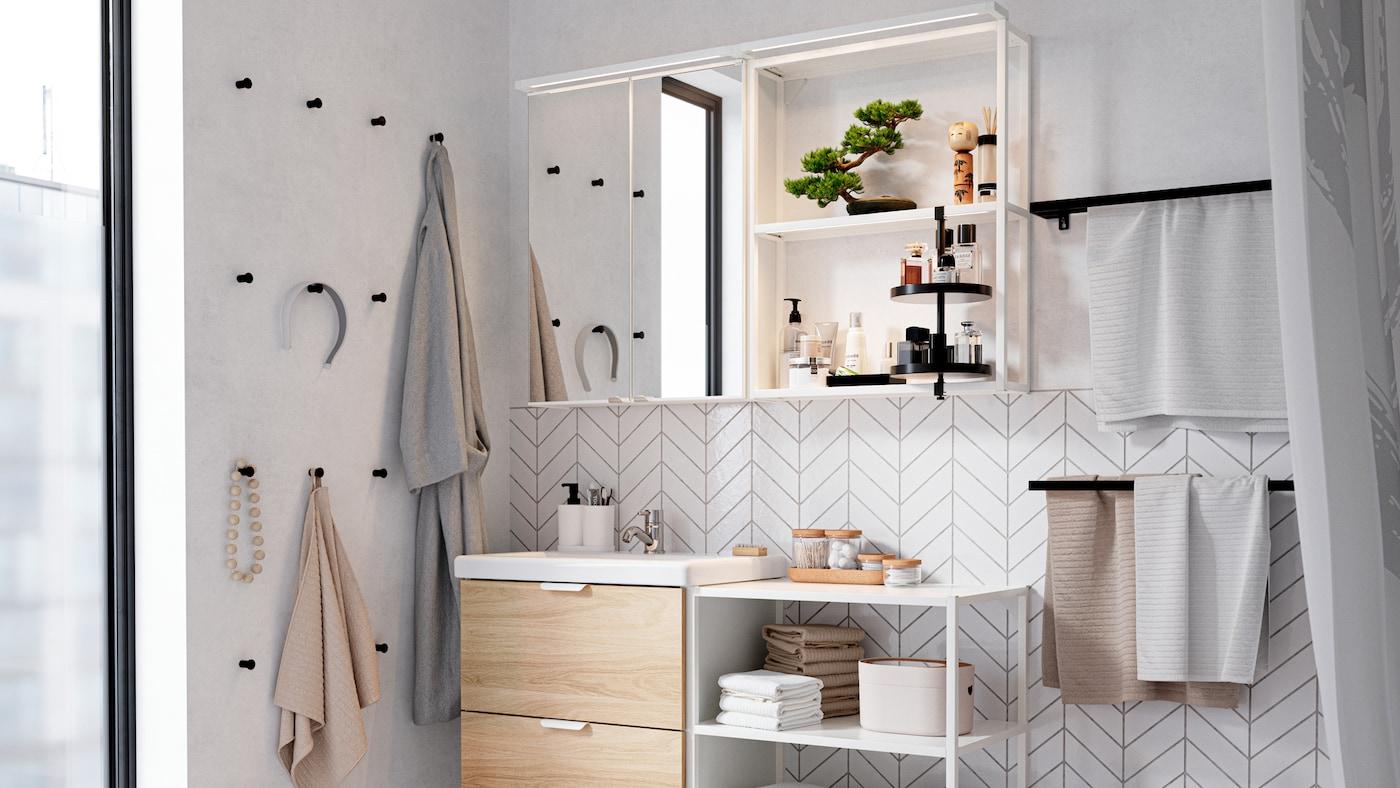 Biały zestawy mebli łazienkowych, czarne haczyki na ścianie, otwarty system przechowywania z ręcznikami, perfumy, drzewko bonsai, szlafrok.