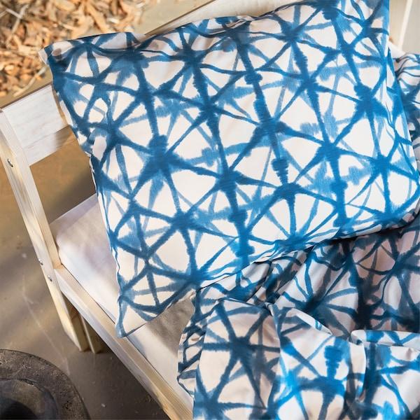 Biancheria da letto STJÄRNFLOCKA con fantasia blu su una struttura letto in legno - IKEA