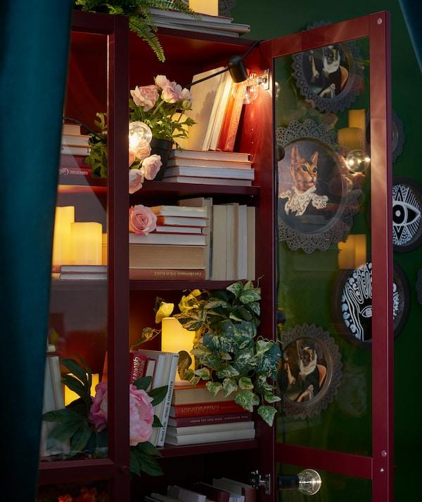 Bibliothèque BILLY rouge à portes vitrées contenant livres, plantes artificielles, bougies et guirlandes lumineuses. Photos encadrées en arrière-plan.