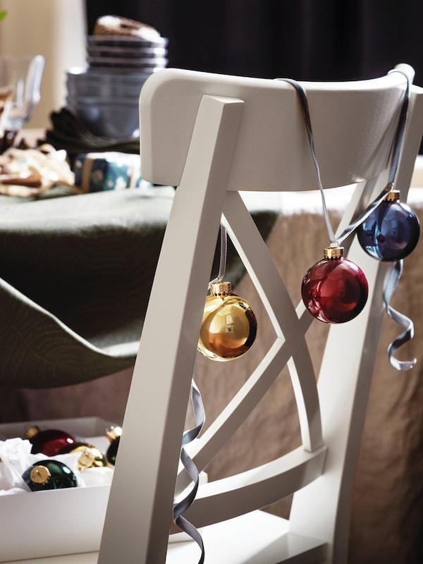 Biela drevená stolička v tradičnom štýle pri jedálenskom stole ozdobená reťazou farebných vianočných gúľ.