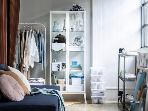 Biela miestnosť s modrou pohovkou, pri stene stojí biely vešiak na oblečenie MULIG a biela vitrína MILSBO. Na zemi je niekoľko priesvitných škatúľ SAMLA.