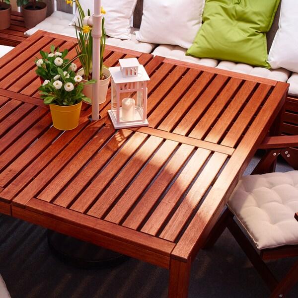 Biela pohovka s vankúšmi a štvorcovým záhradným stolom z hnedej masívnej akácie s dekoráciami navrchu.