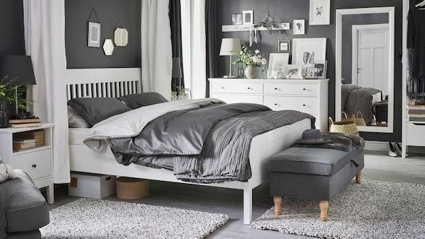 Biela posteľ, nočný stolík a komoda IDANÄS v spálni s posteľnými obliečkami LUKTJASMIN na posteli.