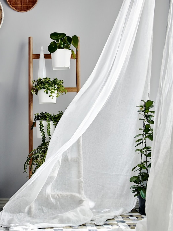 Biela záclona vejúca vo vetre z otvoreného okna.