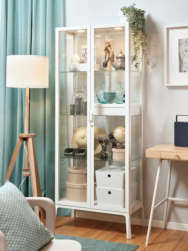 Biela zasklená vitrína MILSBO plná drobností, za ňou biela stena. Vľavo od vitríny je svetlotyrkysový záves, pred ním stojacia lampa LAUTERS. V popredí je stolička s tyrkysovým vankúšom, na podlahe tyrkysový koberec.