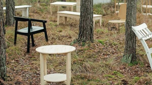 Biele, čierne a svetlohnedé drevené stoly a stoličky rozmiestnené po lese, ktorý je jedným zo zdrojov našich obnoviteľných materiálov.