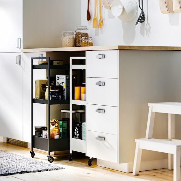 Biele kuchynské skrinky METOD a pracovná doska EKBACKEN, pod ňou sú zasunuté dva vozíky NISSAFORS – jeden čierny, druhý biely.