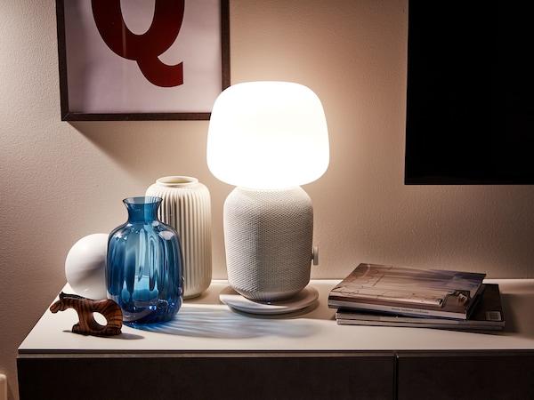 Bielo-sivá lampa SYMFONISK s reproduktorom Wi-Fi vedľa dekorácií a časopisov.
