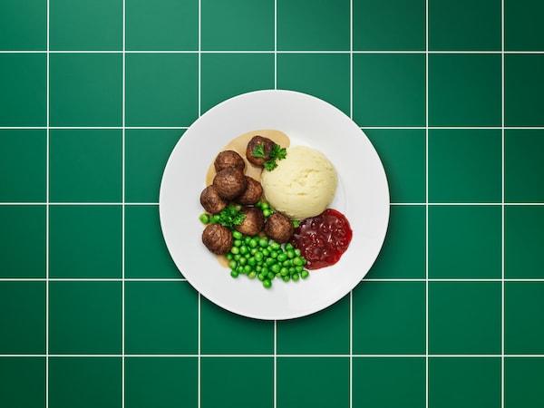 Biely tanier s bezmäsitými guľôčkami, hnedou omáčkou, zemiakovou kašou, brusnicovým džemom, zeleným hráškom a petržlenom.