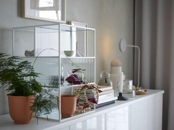 Bijela IKEA SAMMANHANG izložbena kutija od stakla s policama na elementu s biljkama, teglama, knjigama i ukrasnim predmetima.