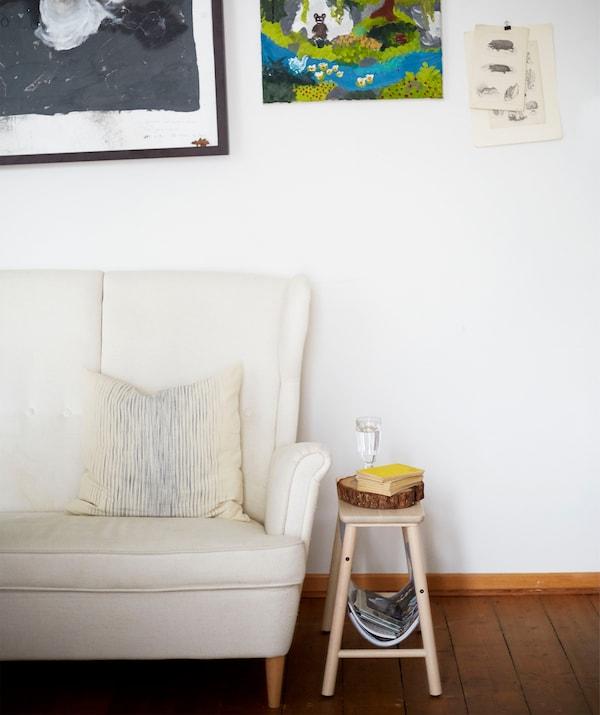 Bijela sofa visokog naslona i mali drveni stolac ispred bijelog zida s umjetninama.