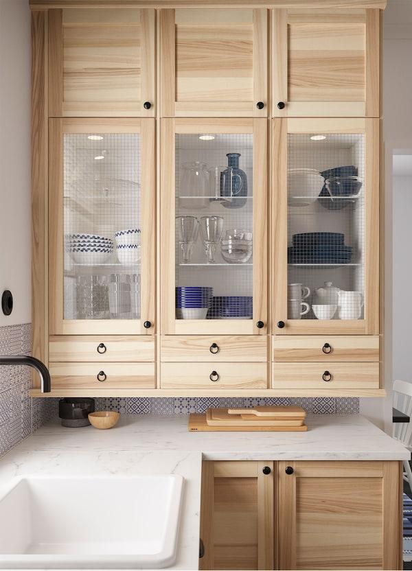 Bijeli IKEA METOD zidni elementi s ugrađenom rasvjetom i TORHAMN staklena vrata od punog jasena u kutu kuhinje.